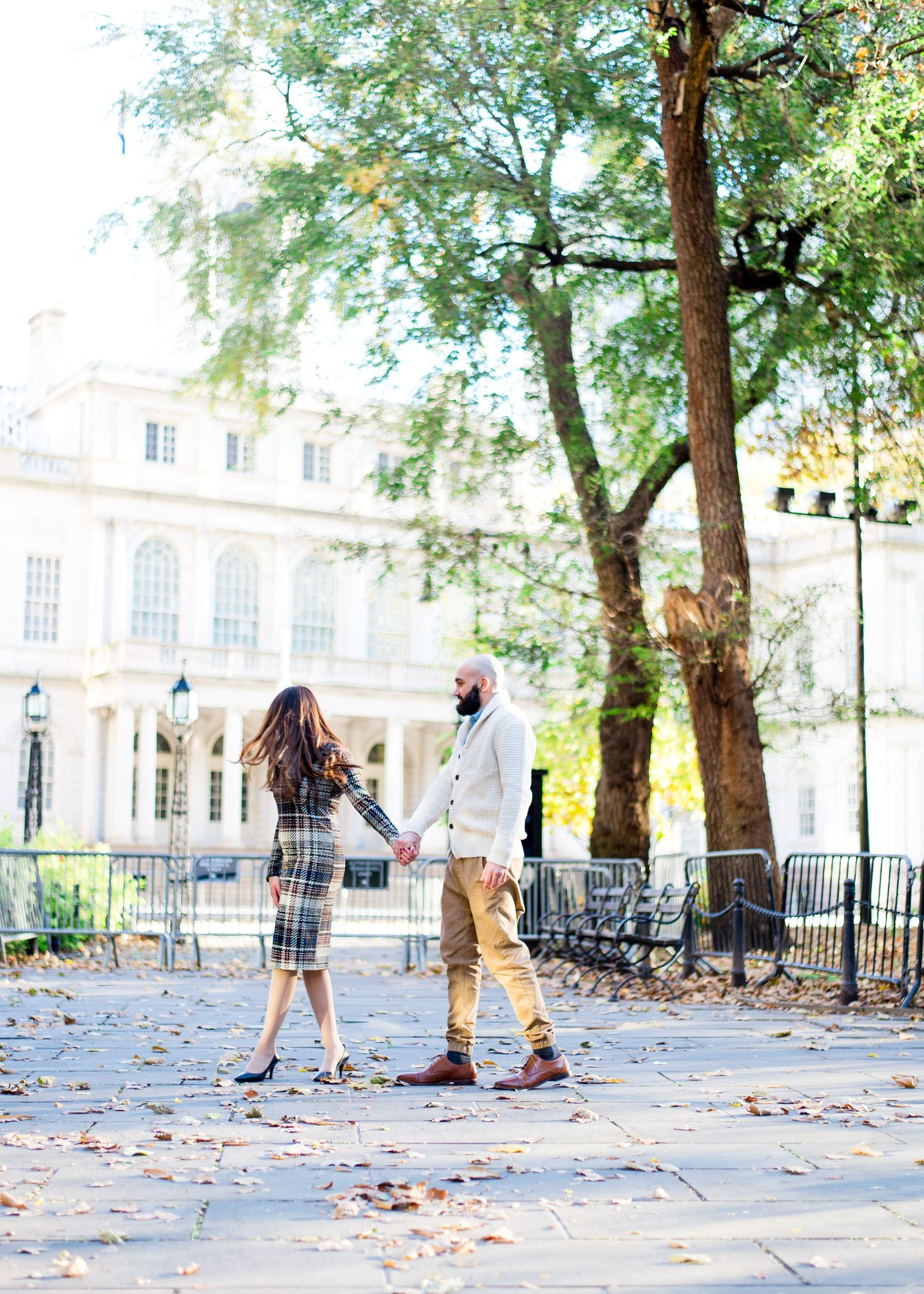 woman in plaid dress holds hand of man in white sweater in front of New York City Hall for engagement pictures