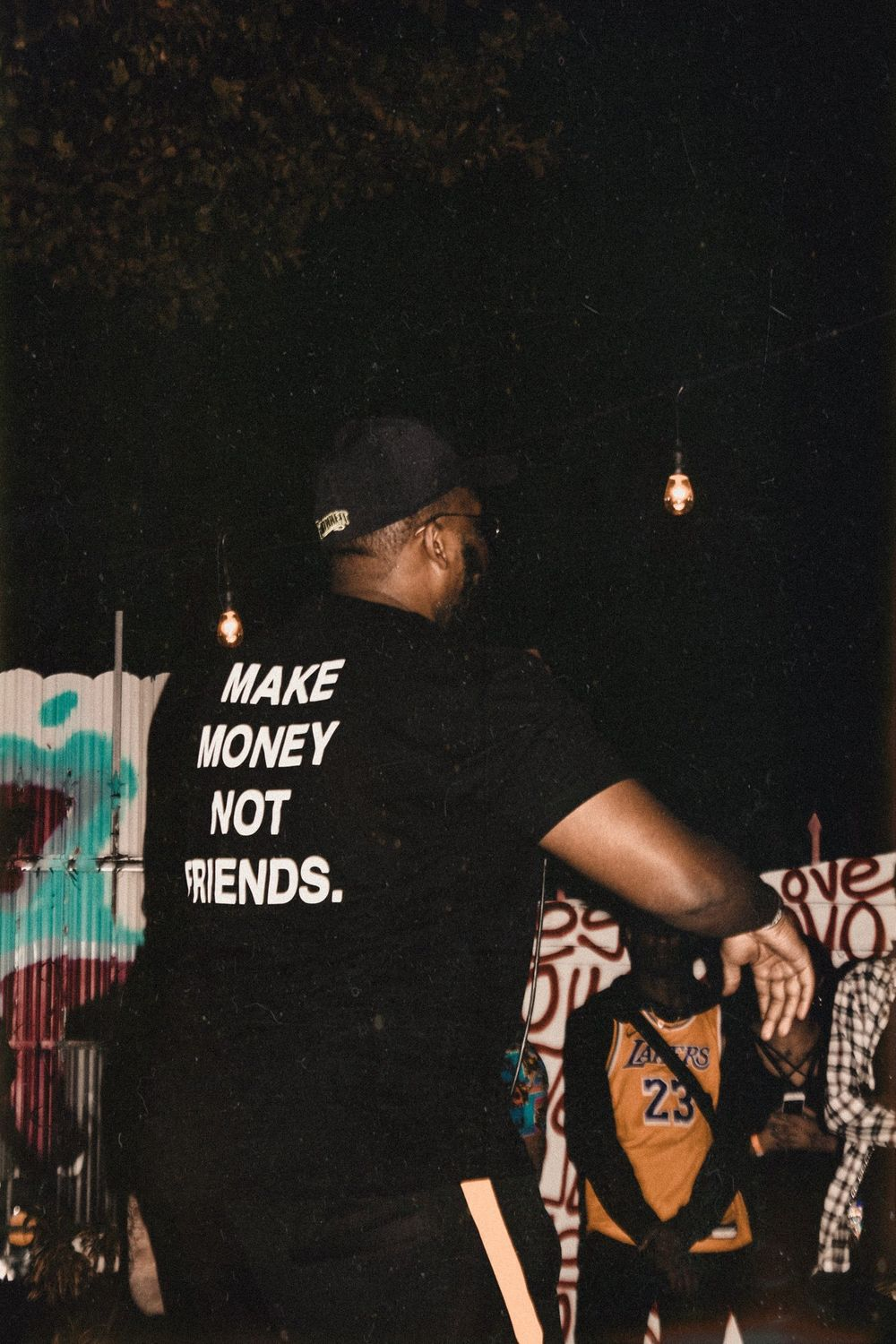 "rapper quentin miller's shirt says ""make money not friends"""