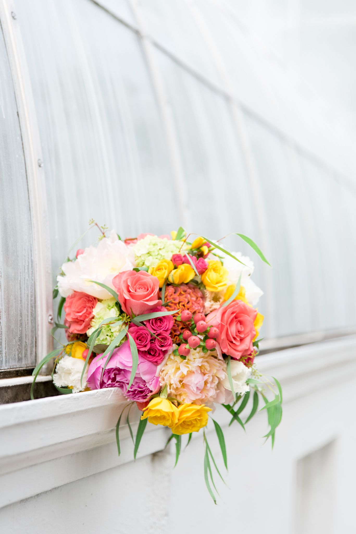 summer wedding bouquet with coral, pink, and yellow mixes roses and peonies against a glass conservatory window