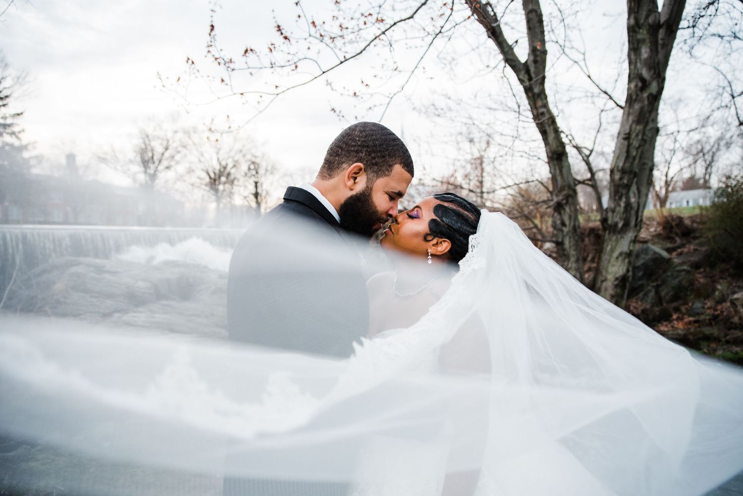 wedding veil bride and groom kiss