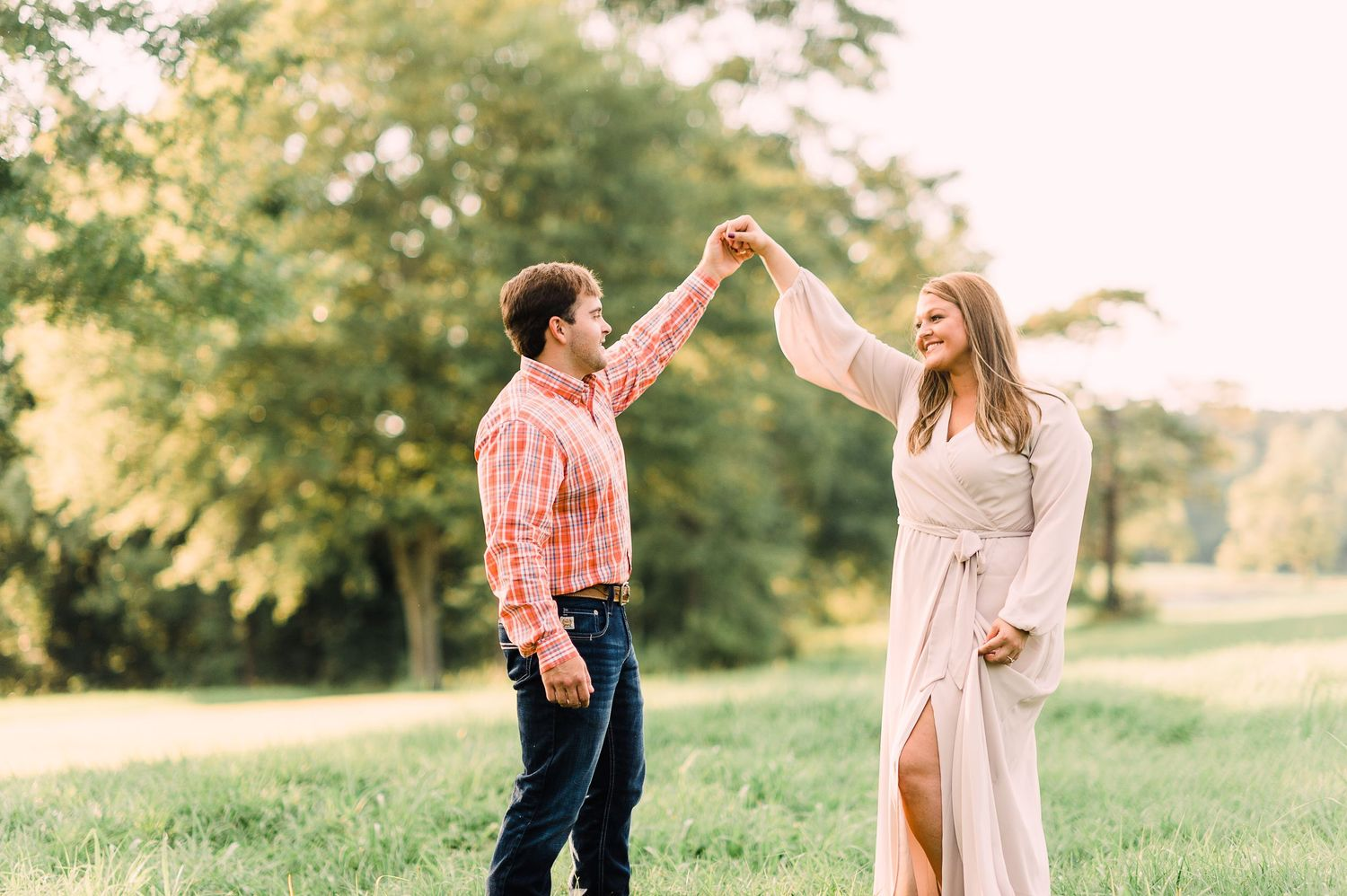 engaged couple dancing in a field