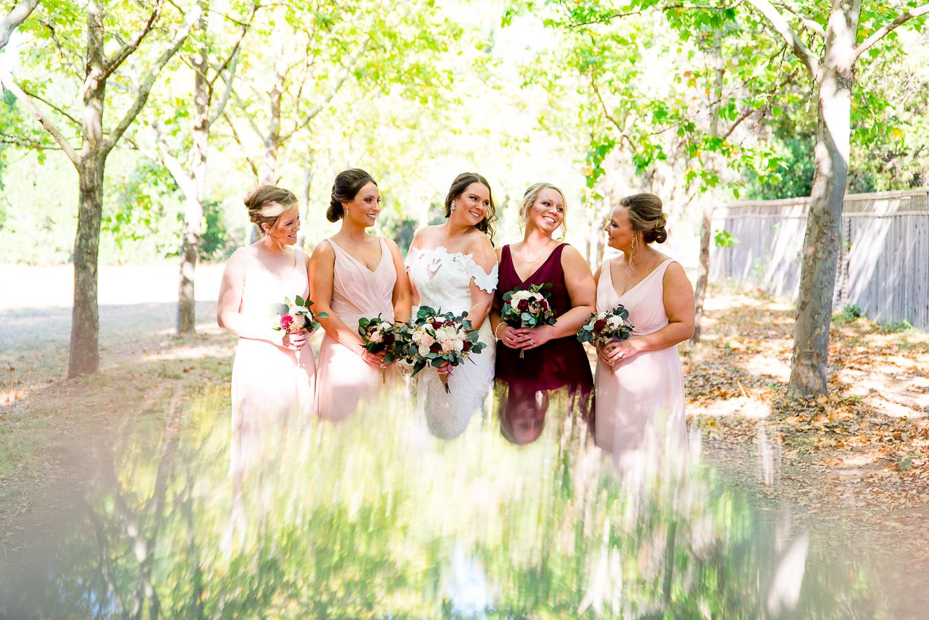 bride and bridesmaids smile at each other in blush and red bridesmaids dresses for a fall wedding in Northern California