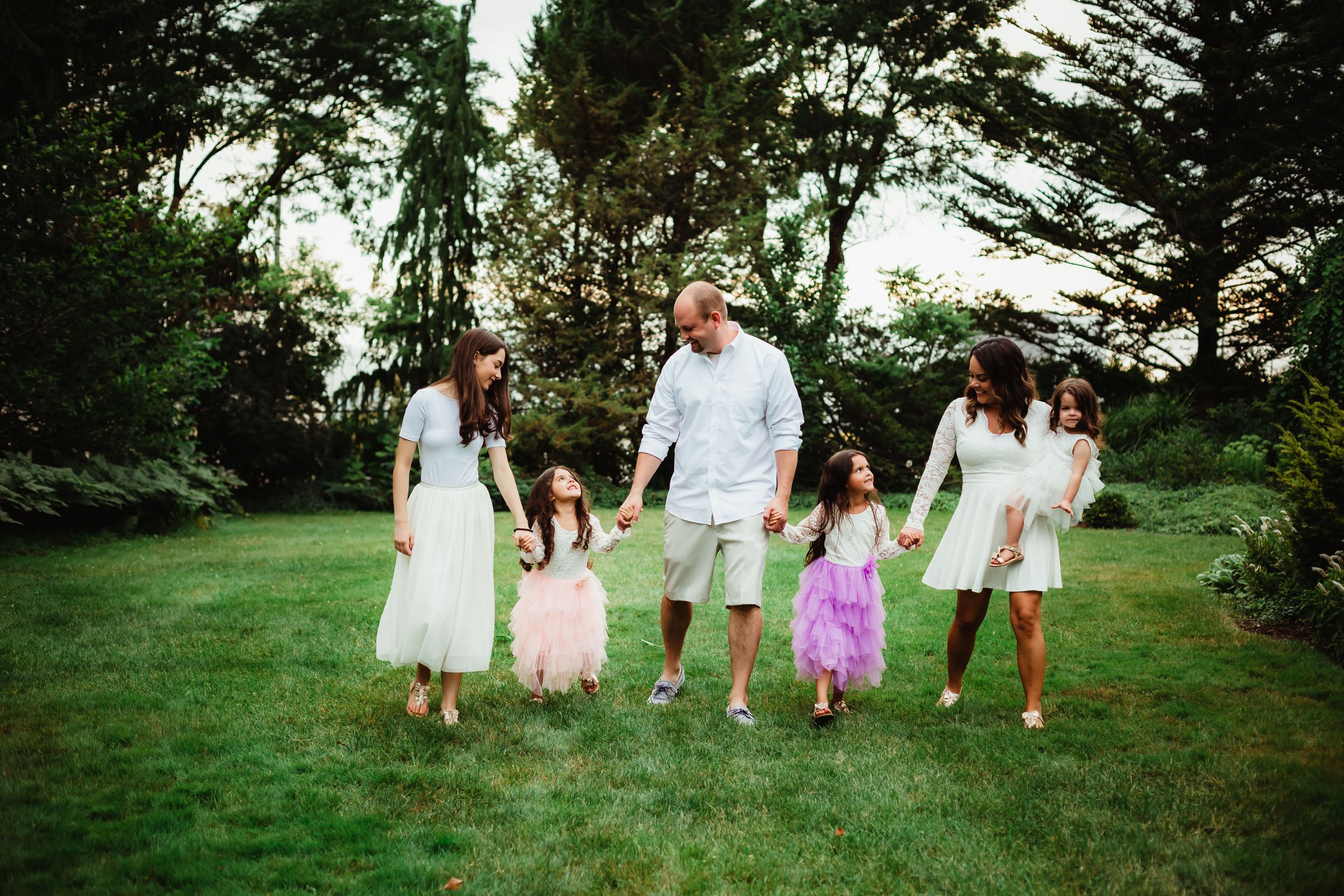 A family with four daughters of various ages holding hands walking through Cooley Gardens.