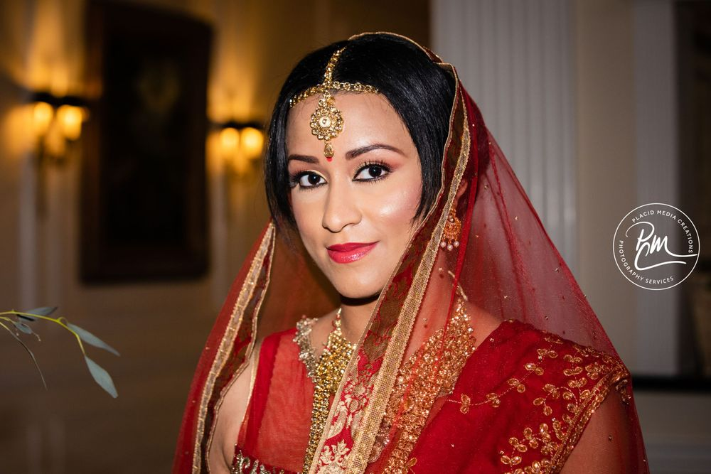 The bride draped with an extravagant head scarf and a large amount of jewelry.