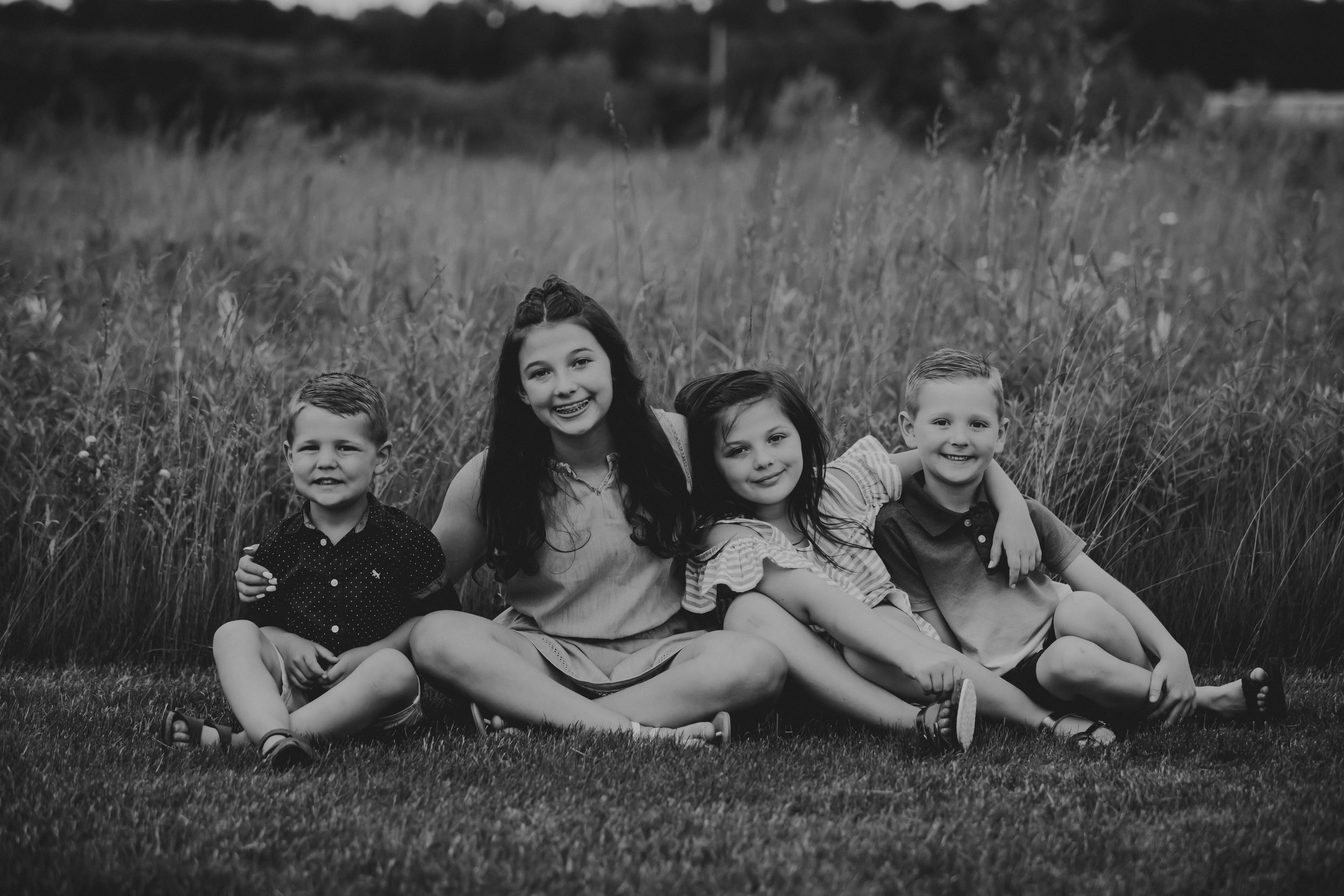 Black and white photo of four children sitting in front of a field smiling.