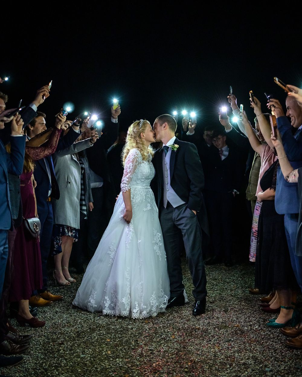 Bride and groom surrounded by quests with mobile phome torches