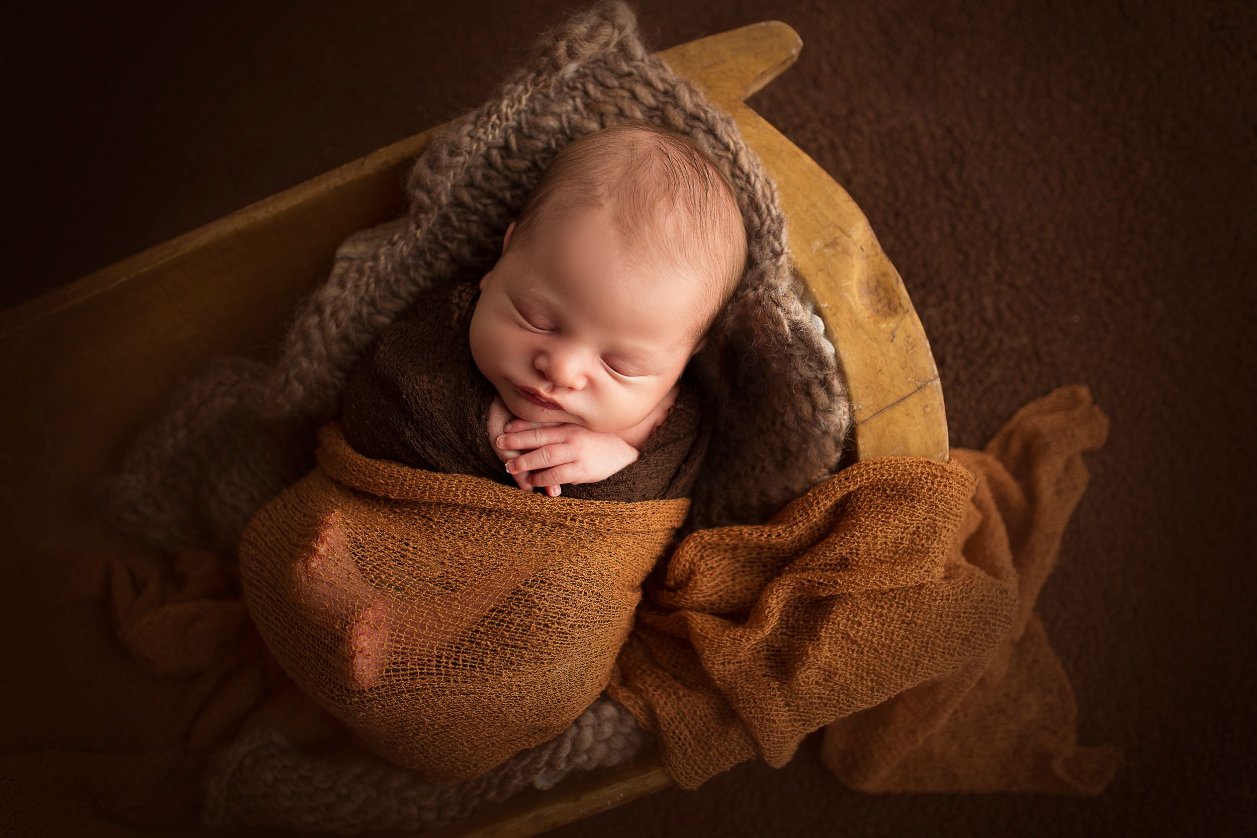 sleeping newborn boy wrapped in brown blanket in bowl