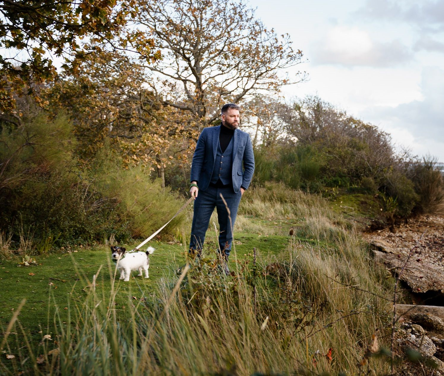 Groom in a blue tweed three piece suit and a roll neck jumper with his pet jack russell. Hampshire wedding photography.