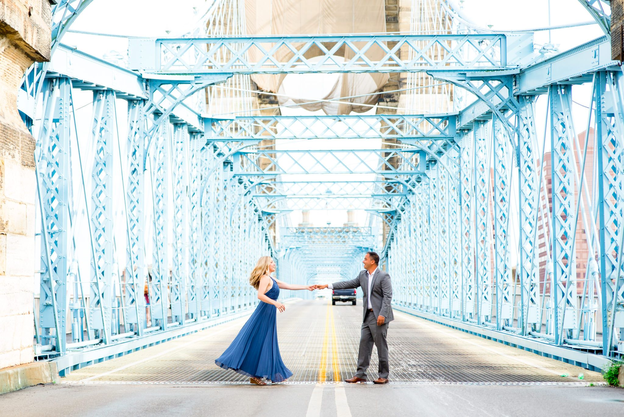 man in gray suit holds hand of woman in long blue dress on Roebling Bridge engagement pictures