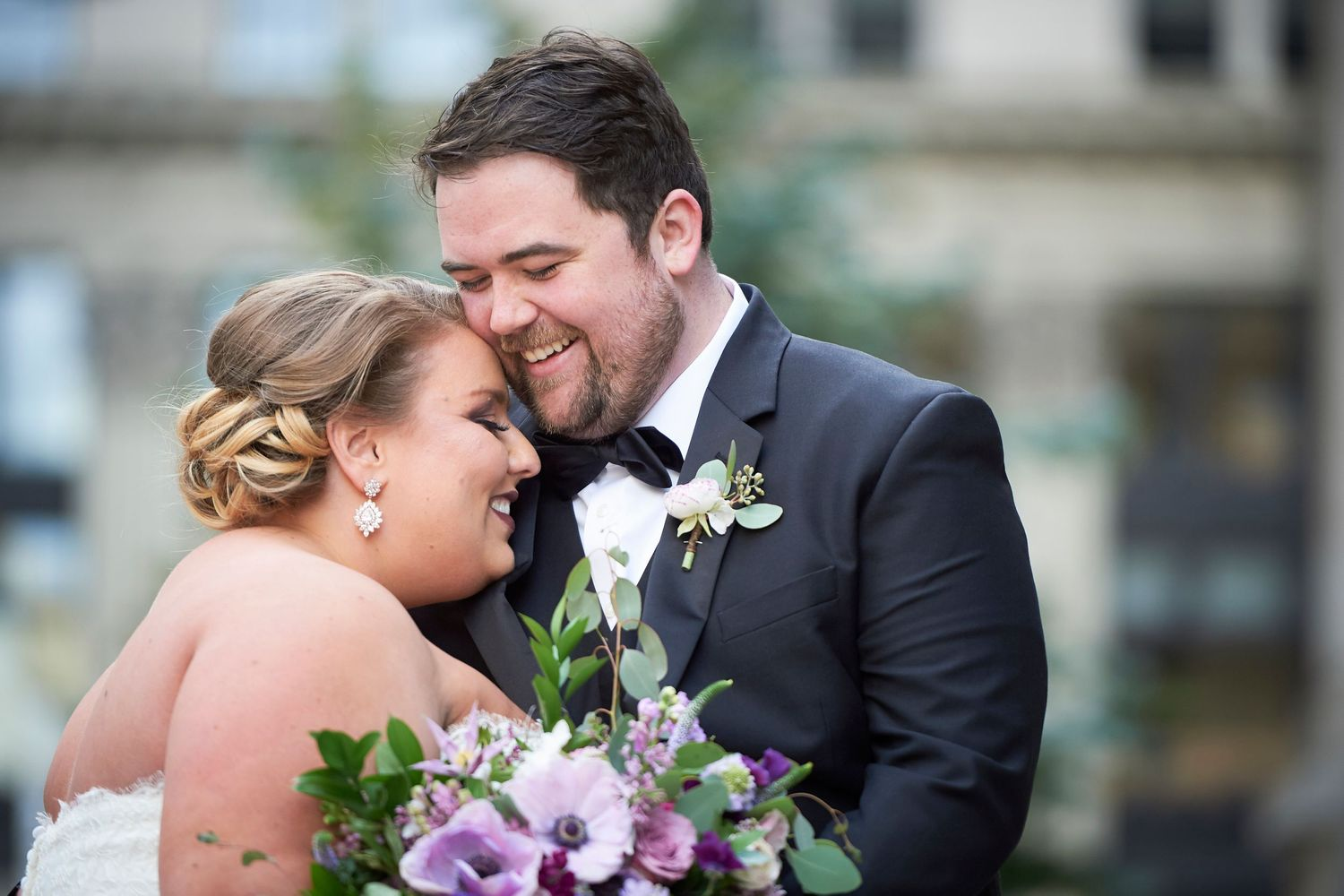 bride and groom laugh and nuzzle and laugh outside philadelphia city hall
