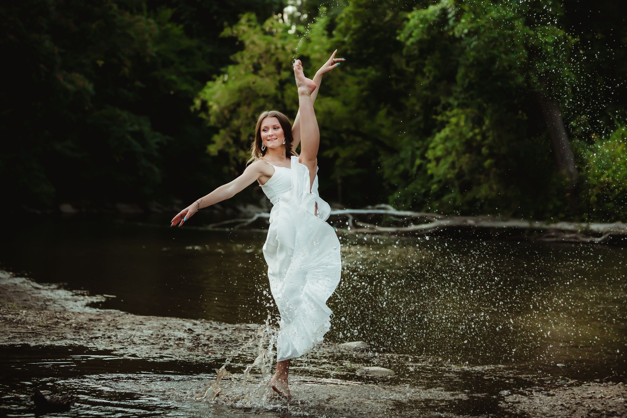 Teenage girl in a white dress kicking her leg up into a dance pose in the river. Water droplets follow the path.