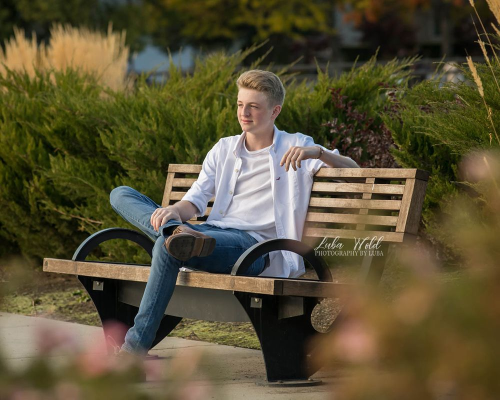 high school senior boy sitting on a bench in Coeur d' Alene photographer luba wold