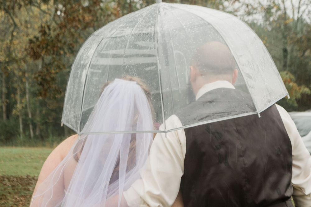 Bride and Groom cuddle under clear umbrella rainy wedding day Bowdon GA 2020 Wedding