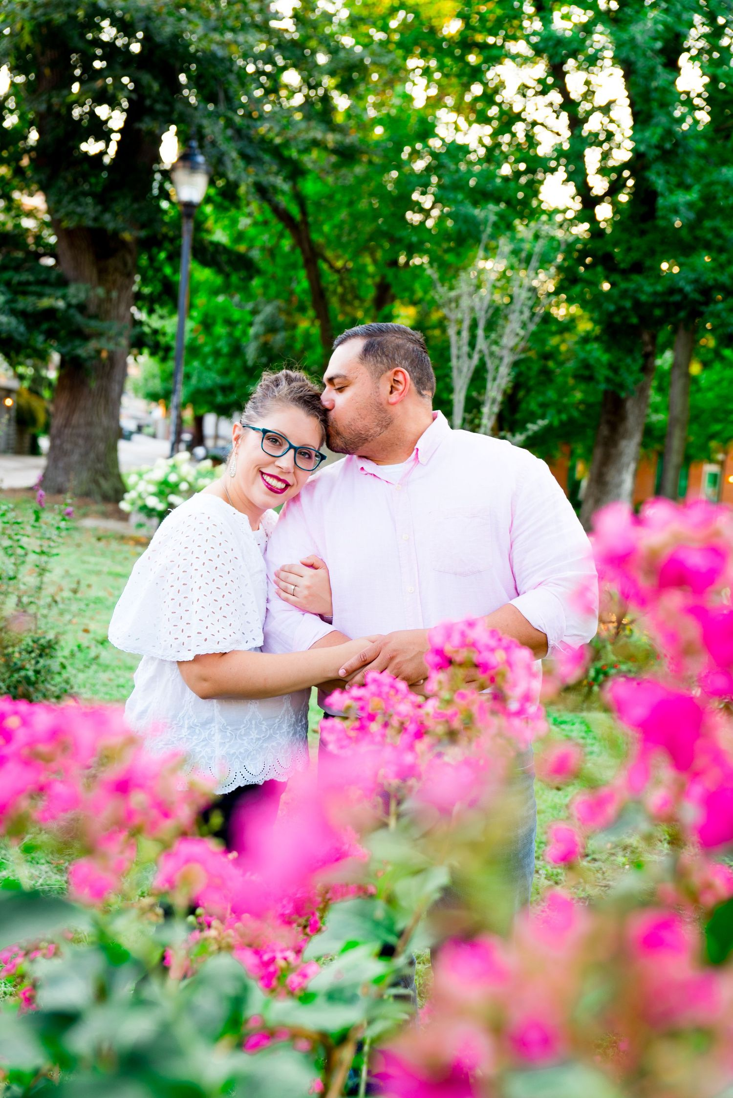man kisses his fiancee's forehead as she holds him and smiles standing behind a pink flower bush