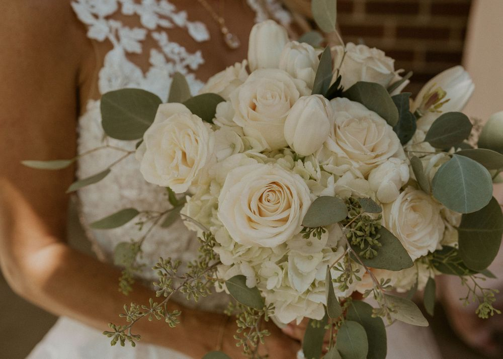 Bride carries her bouquet of white and blush roses and hydrangeas