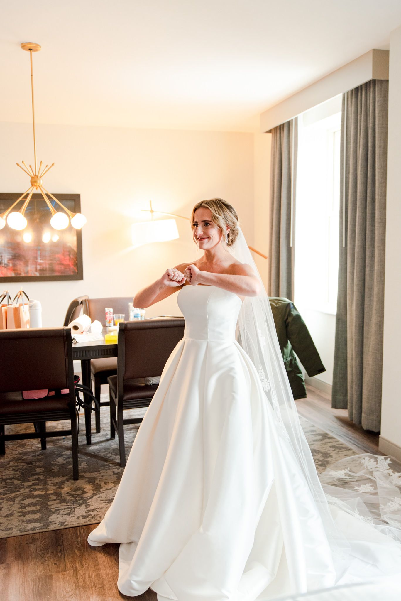 blonde bride dancing in hotel room after the first look with her bridesmaids