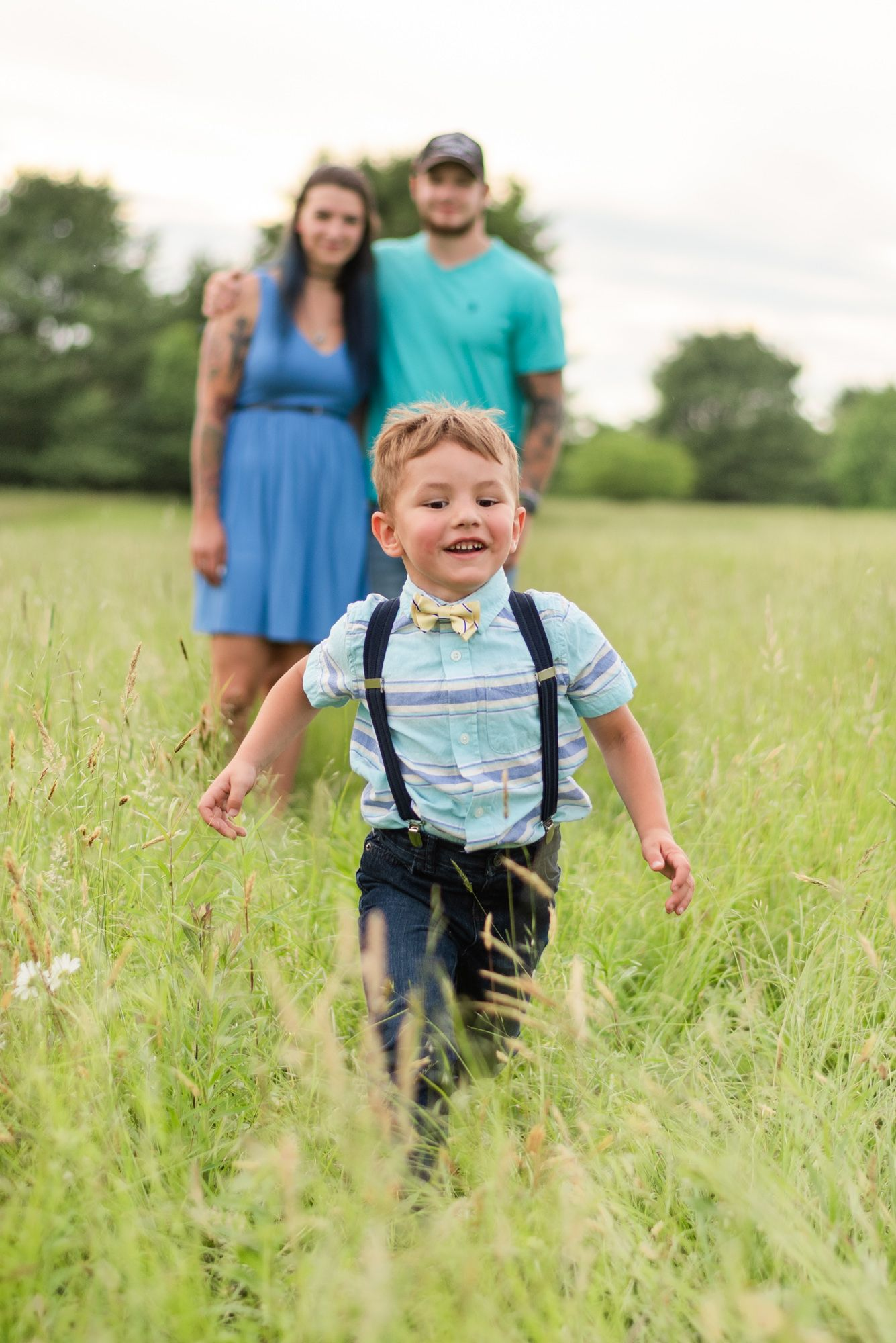 Little boy running through field and parents standing in background in Clarion Pennsylvania