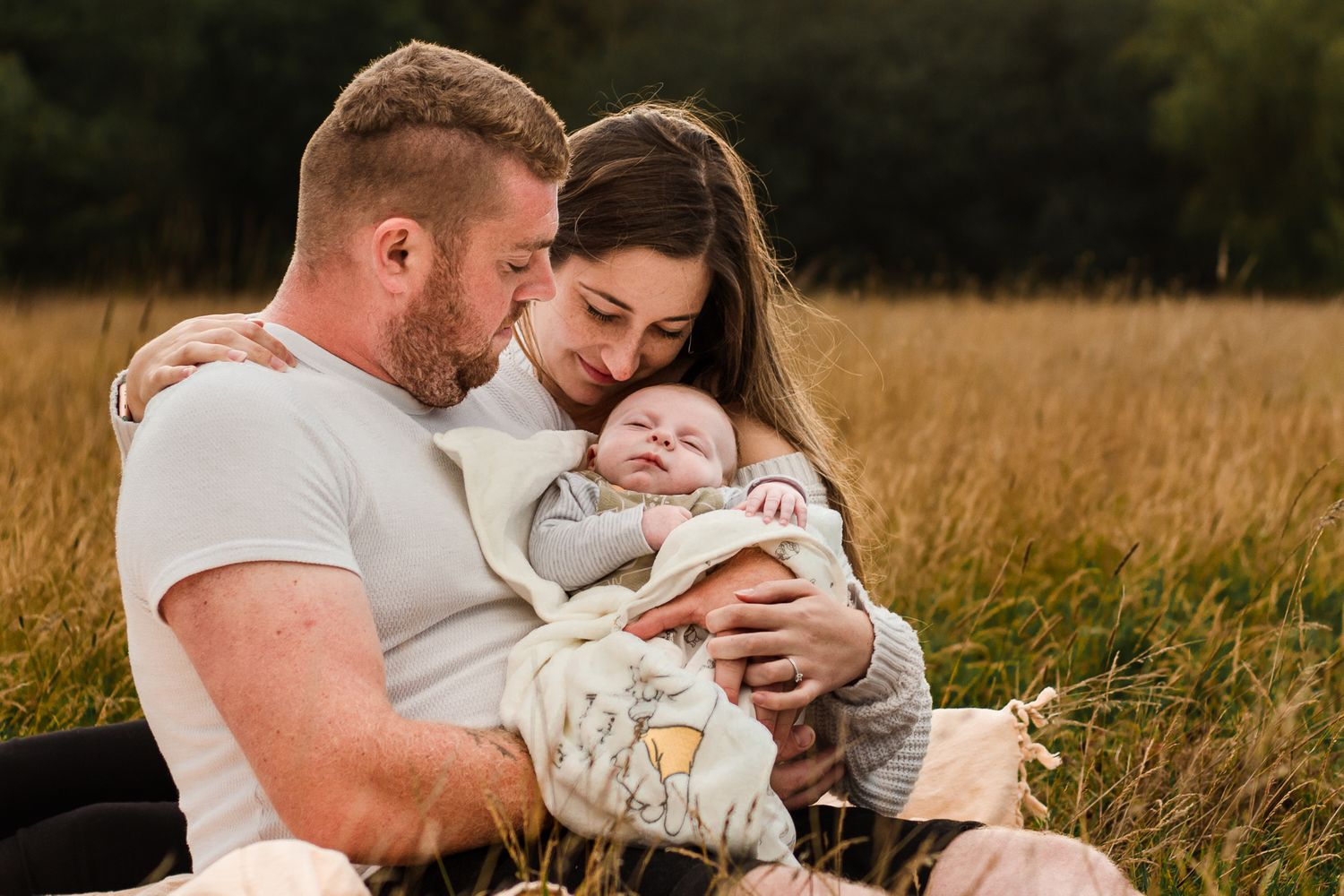 In a field in Havant new parents sit in the long grass snuggling their newborn baby boy.