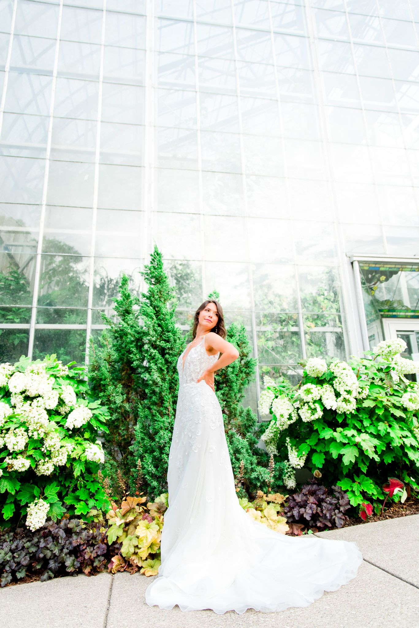 dark haired bride in KF Serafina Gown stands with hands on hips at Krohn Conservatory wedding