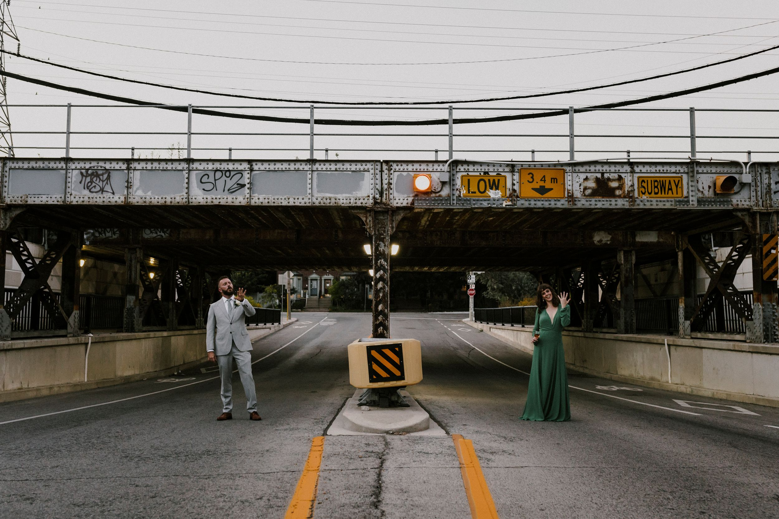 Nontraditional Toronto couple at underpass showing off their wedding rings and holding drinks. Green wedding dress.