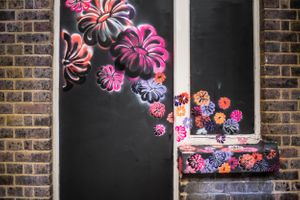 Flower Power graffiti on door and brick wall in London's Shoreditch neighborhood.