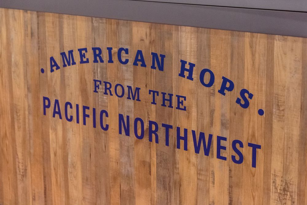 american hops from the pacific northwest printed on the front of the stand at beerx