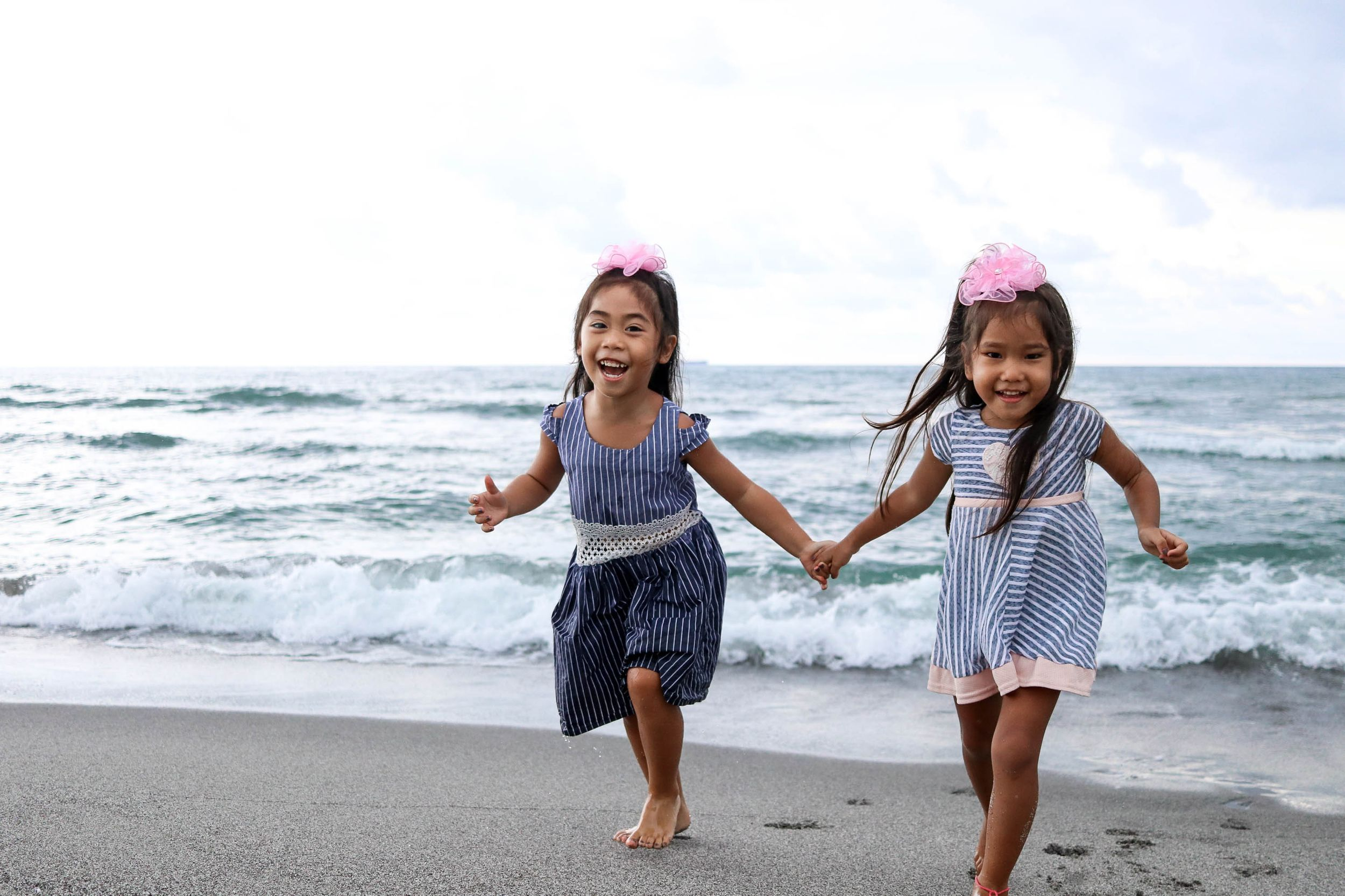 two sisters running on the beach