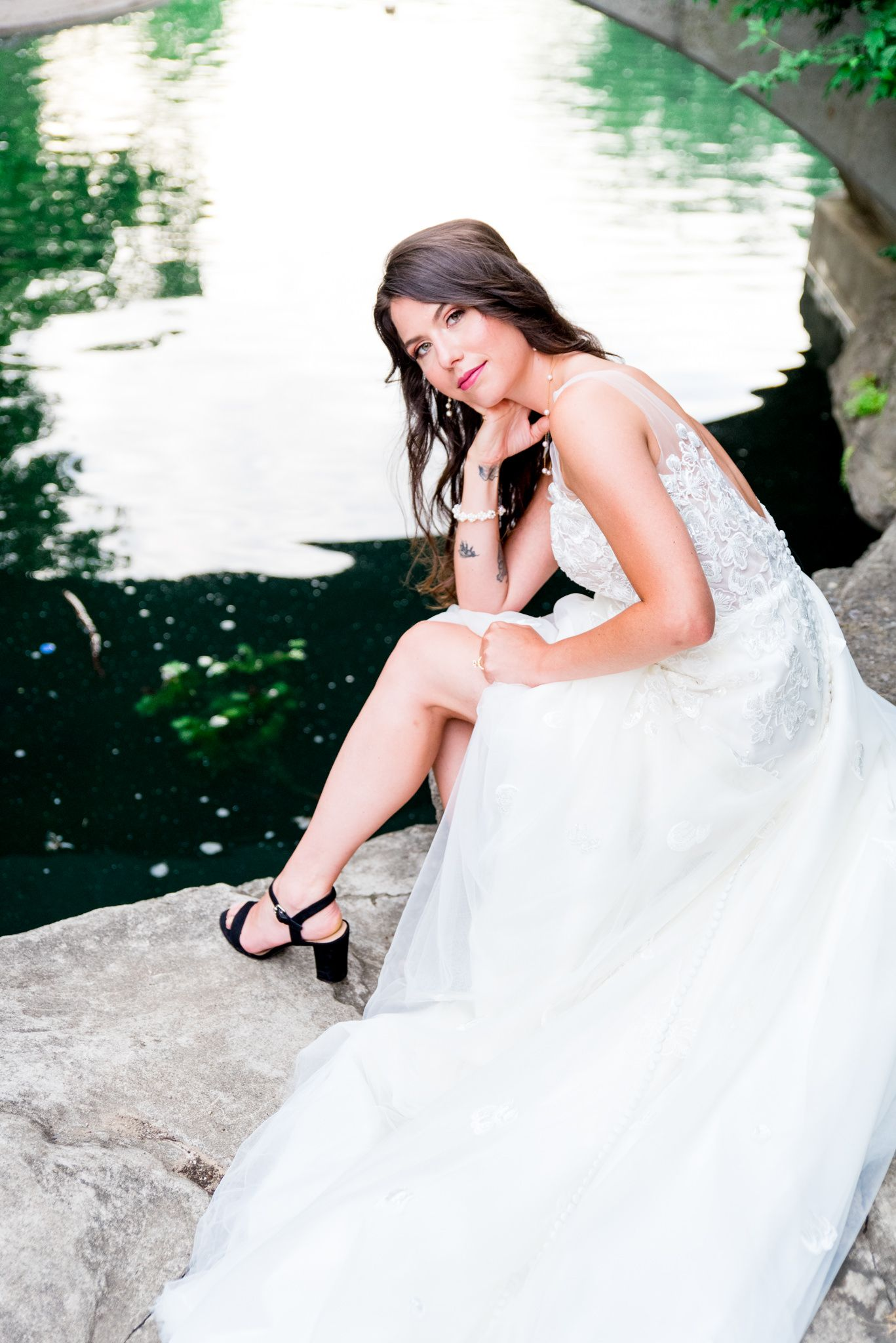 bride in black heels leans onto her knee, wedding dress fanned out showing off her leg