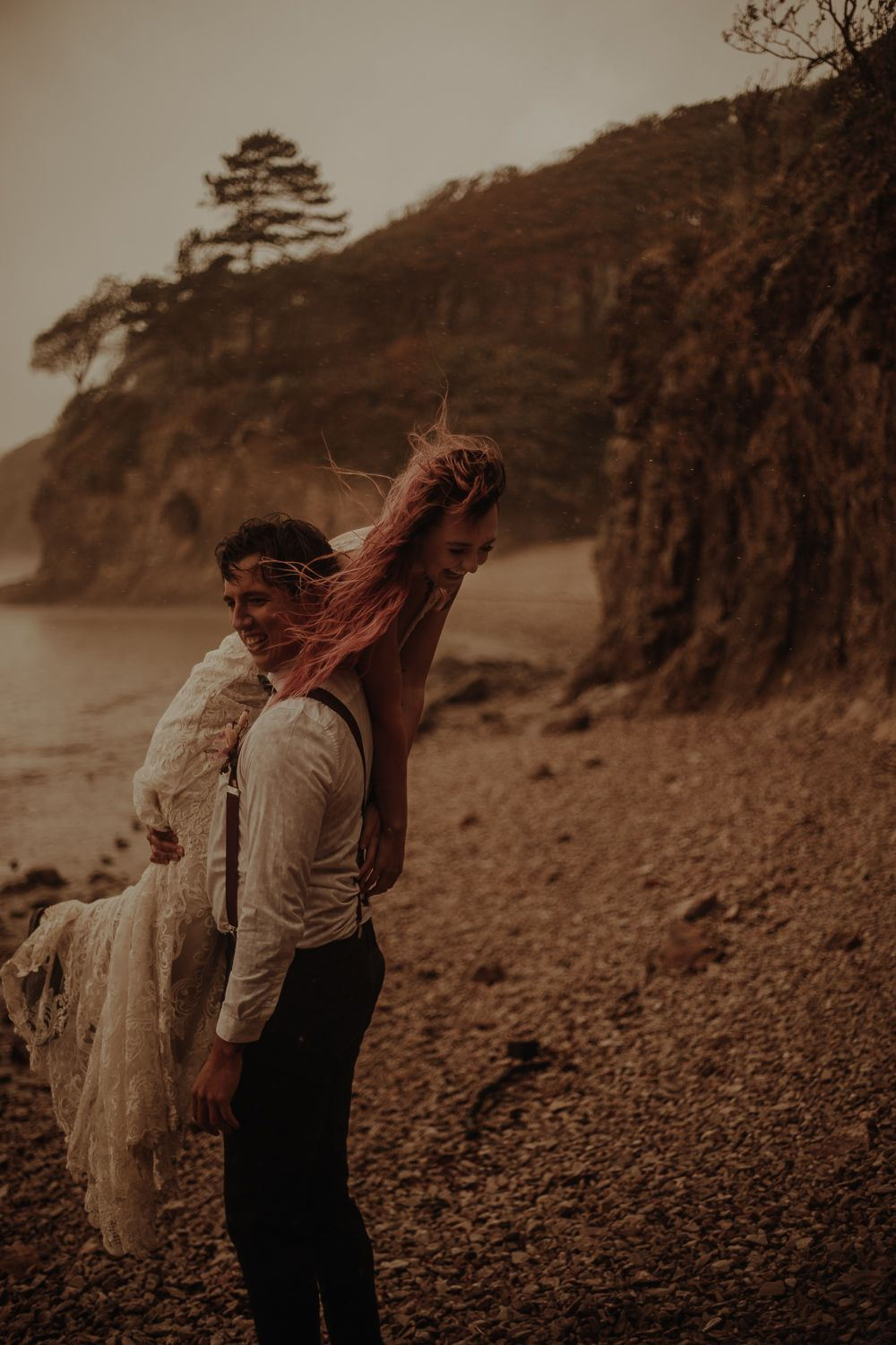 Groom lifting bride at elopement wedding on the beach