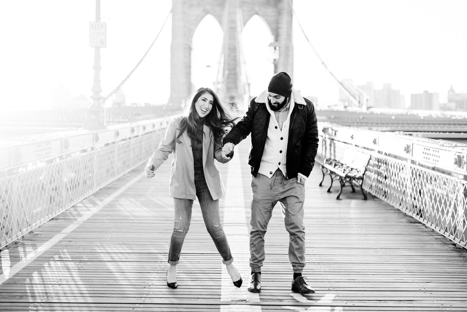 black and white photo of an engaged couple walking and laughing along Brooklyn Bridge in NYC at sunrise