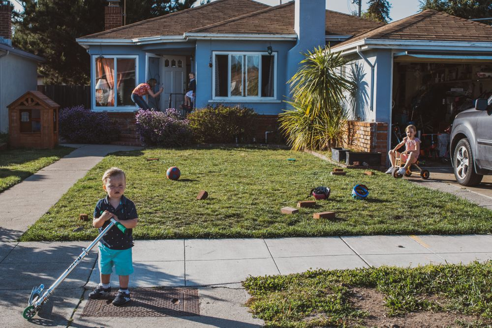 Children play in the front yard while a mom takes a photo of her daughter at the back of the house in Alameda, CA