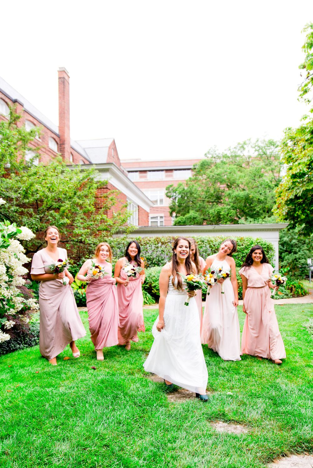 bridesmaids in blush dresses laugh and walk through garden at Woman's Club of Evanston fall wedding