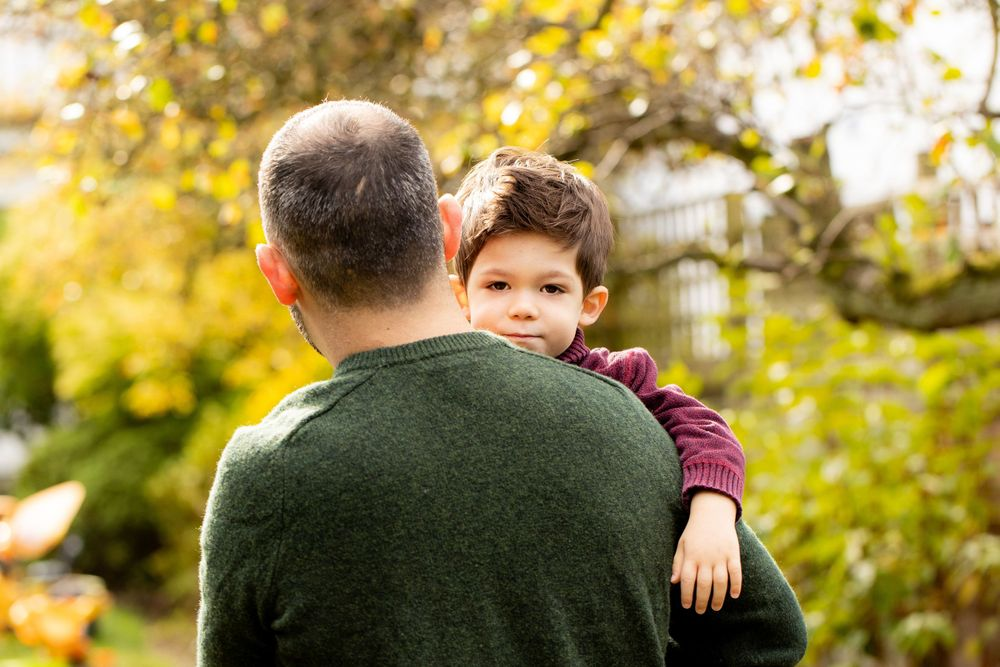 A young boy looks at the camera as he hugs his father in their garden - Family Photography