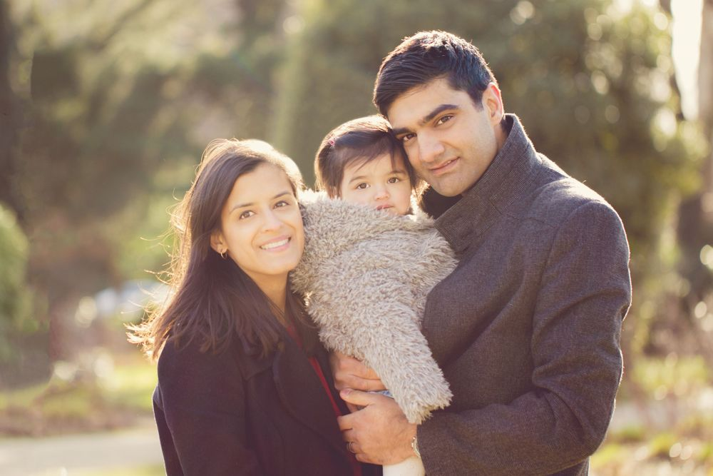 A mother and father pose with their baby daughter in the park - Family Photography