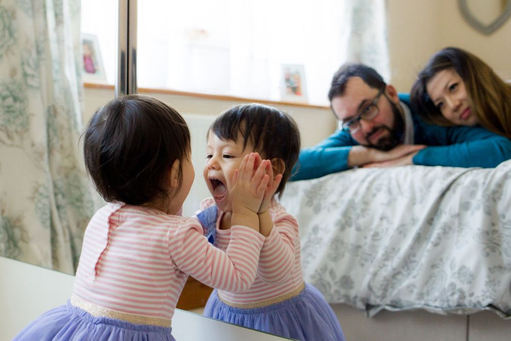 A little girl makes fun faces in the mirror as her parents watch her - Family Photography