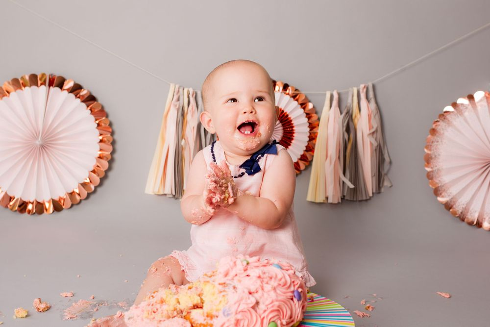 A baby girl claps her hands together during her cake smash photo shoot - Family Photography
