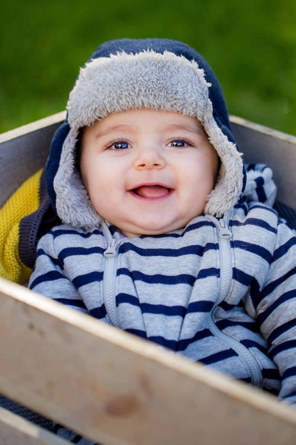 A baby boy smiles at the camera whilst sitting in a wooden crate in his garden - Family Photography