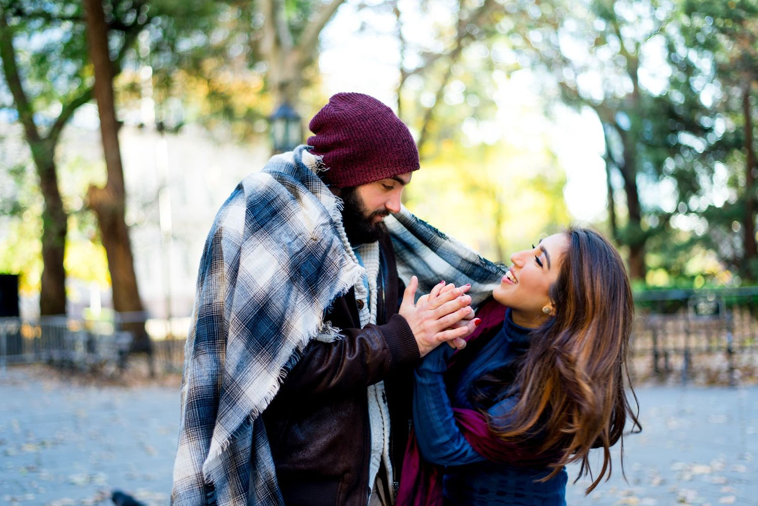 young engaged couple wrapped in navy plaid blanket holding hands and smiling for engagement pictures in NYC