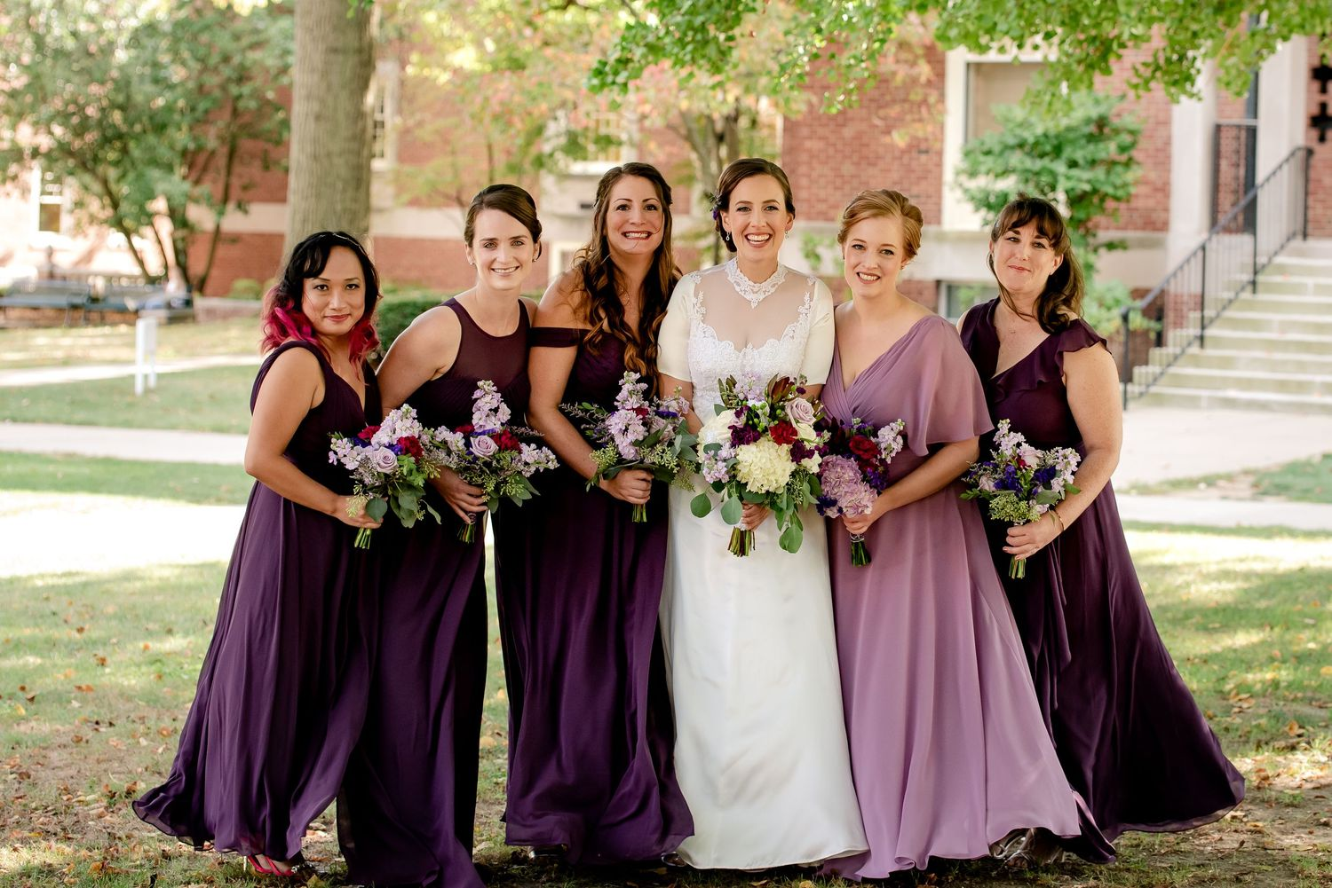 bridal party in pittsburgh with bridesmaids wearing maroon and purple holding bouqets