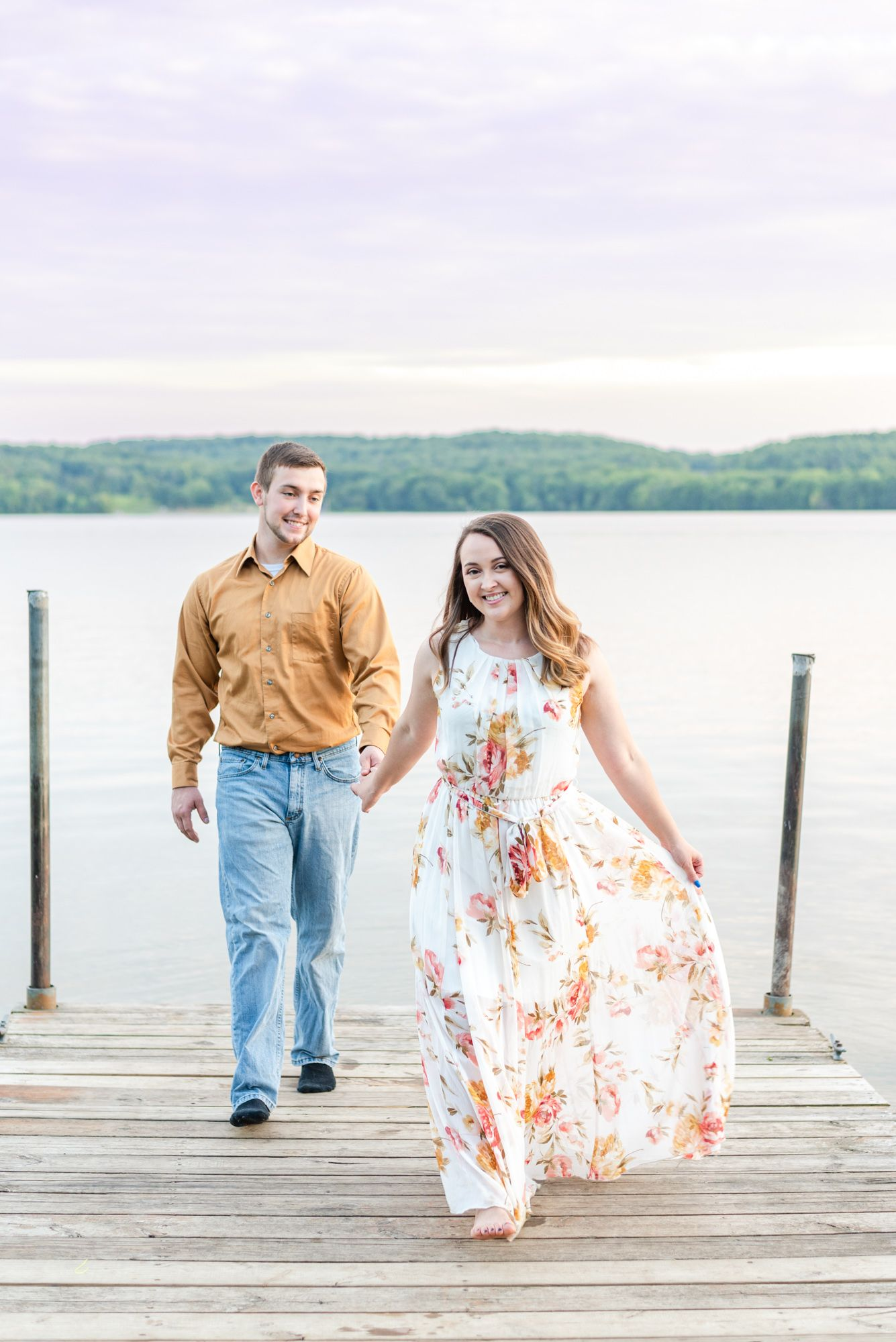 Couple walking for engagement on dock of Lake Arthur at Moraine State Park in Pennsylvania