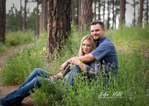 engaged couple at a park in Post Falls Idaho sitting in a spring field of flowers photographer luba wold engagement