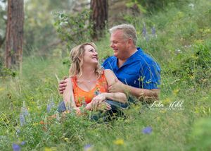 engagement photo of a couple in spring flower field on Tubbs Hill in Coeur d' Alene photographer luba wold