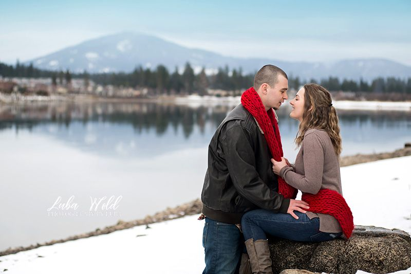 engaged couple by Spokane river looking at each other photographer luba wold in coeur d alene