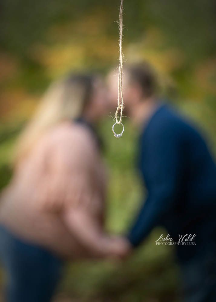 spokane engaged couple kissing engagement ring photographer luba wold in Manito park