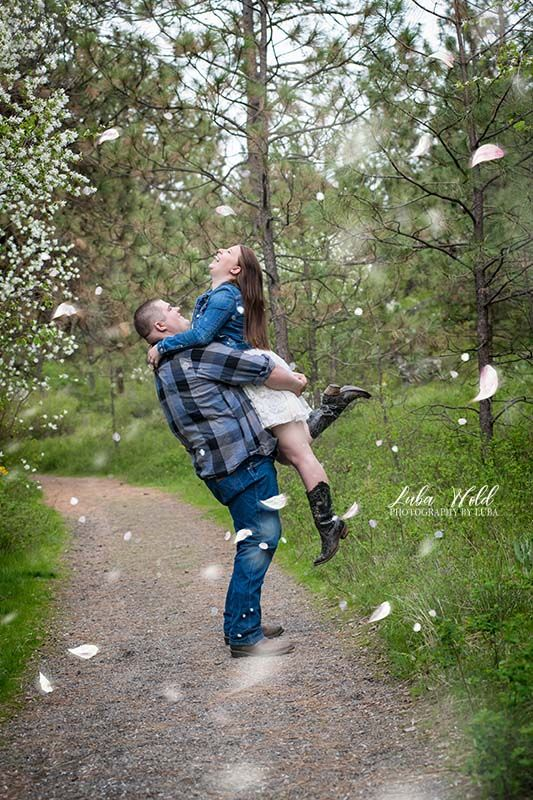 happy engaged playful couple in spring with white petals at Manito Park in Spokane photographer luba wold
