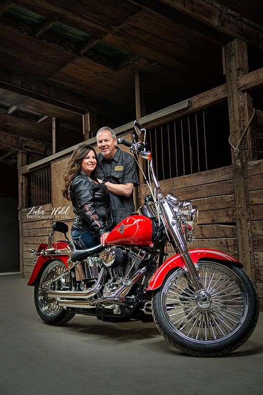 engagement photo of a couple by a red Harley Davidson motorcycle in Liberty Lake Washington photographer luba wold