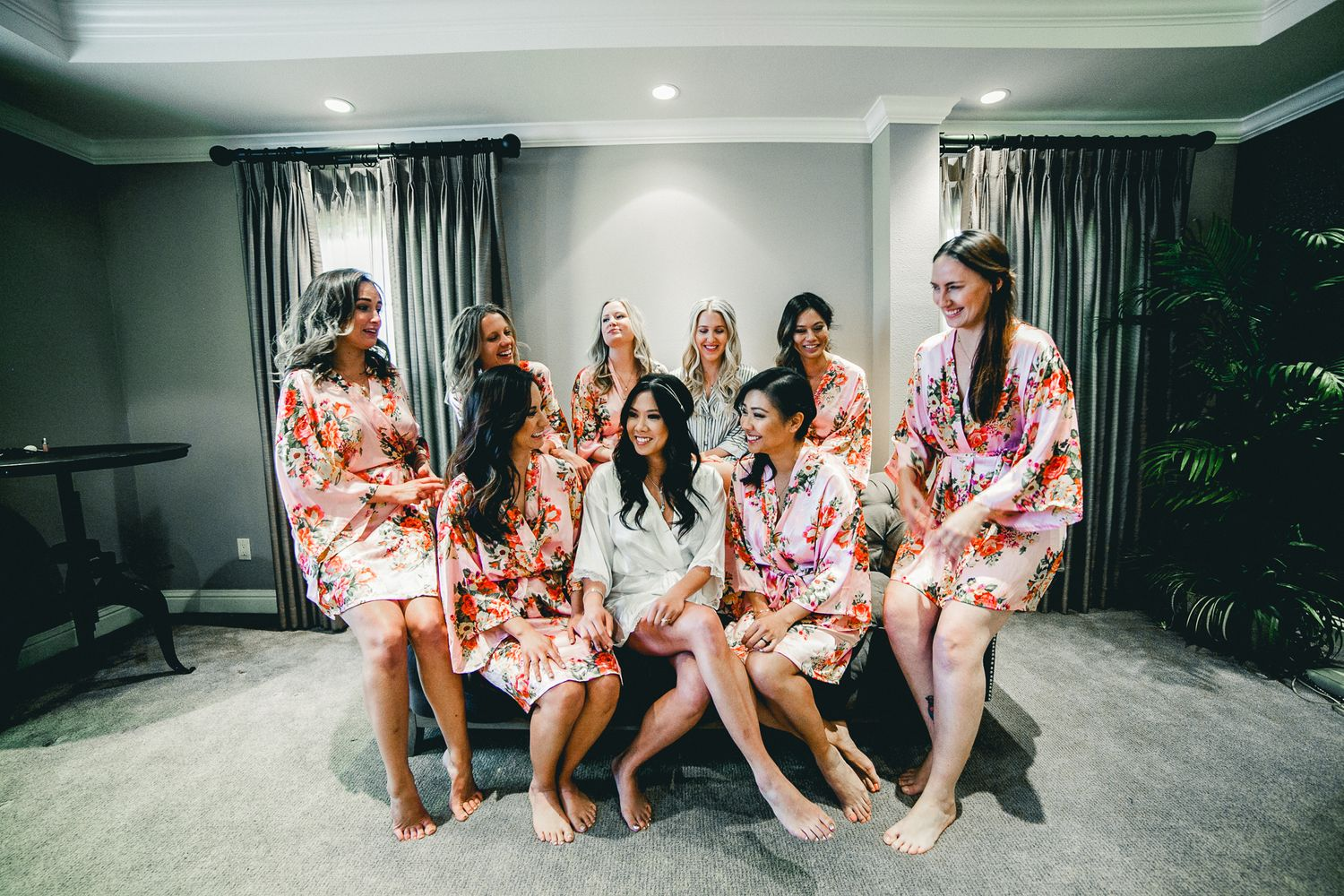 bridal party sitting on couch with bride in robes