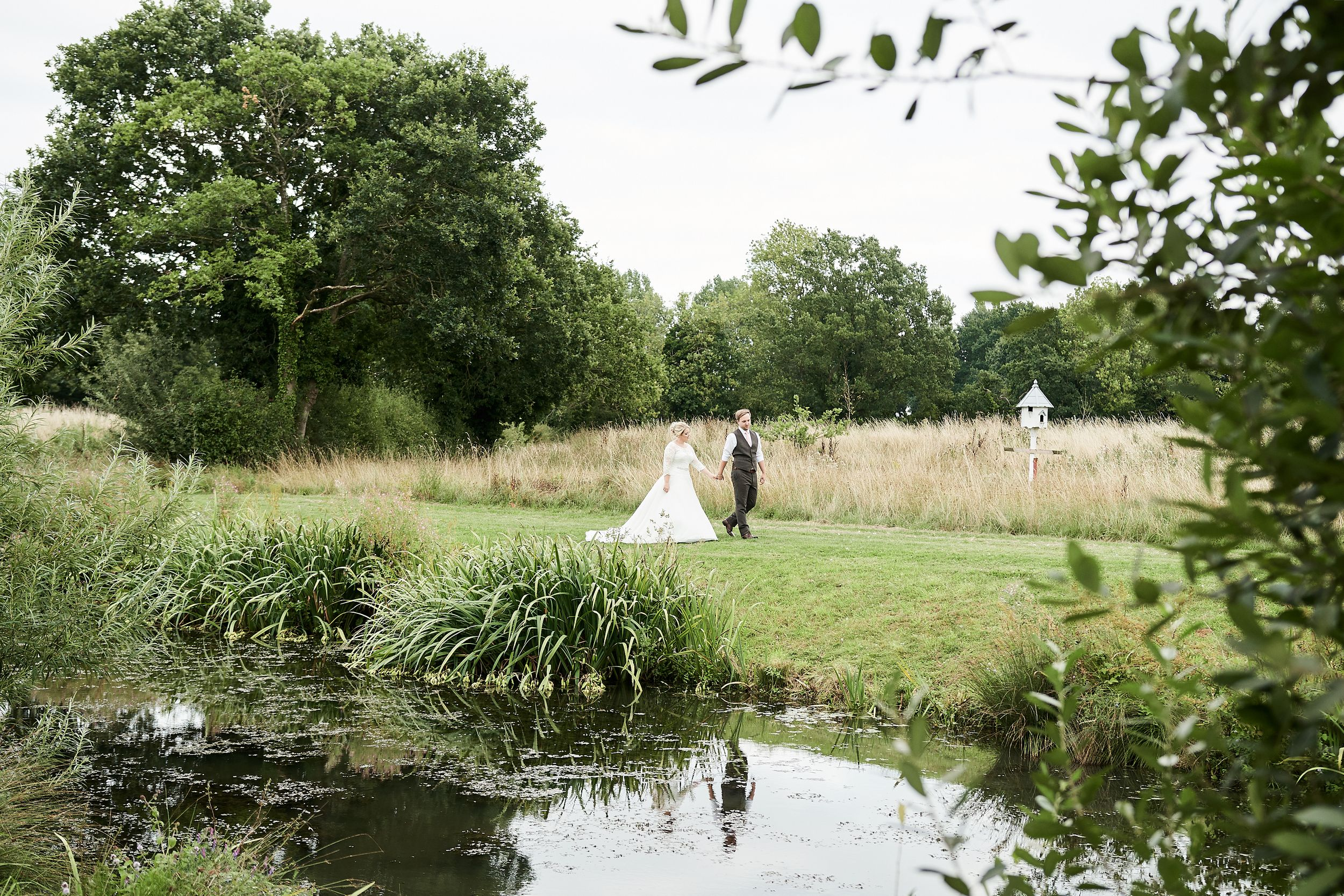 bride and groom walk by lake at Old Buckingham Country Park by Norfolk Wedding Photographer Faye Amare