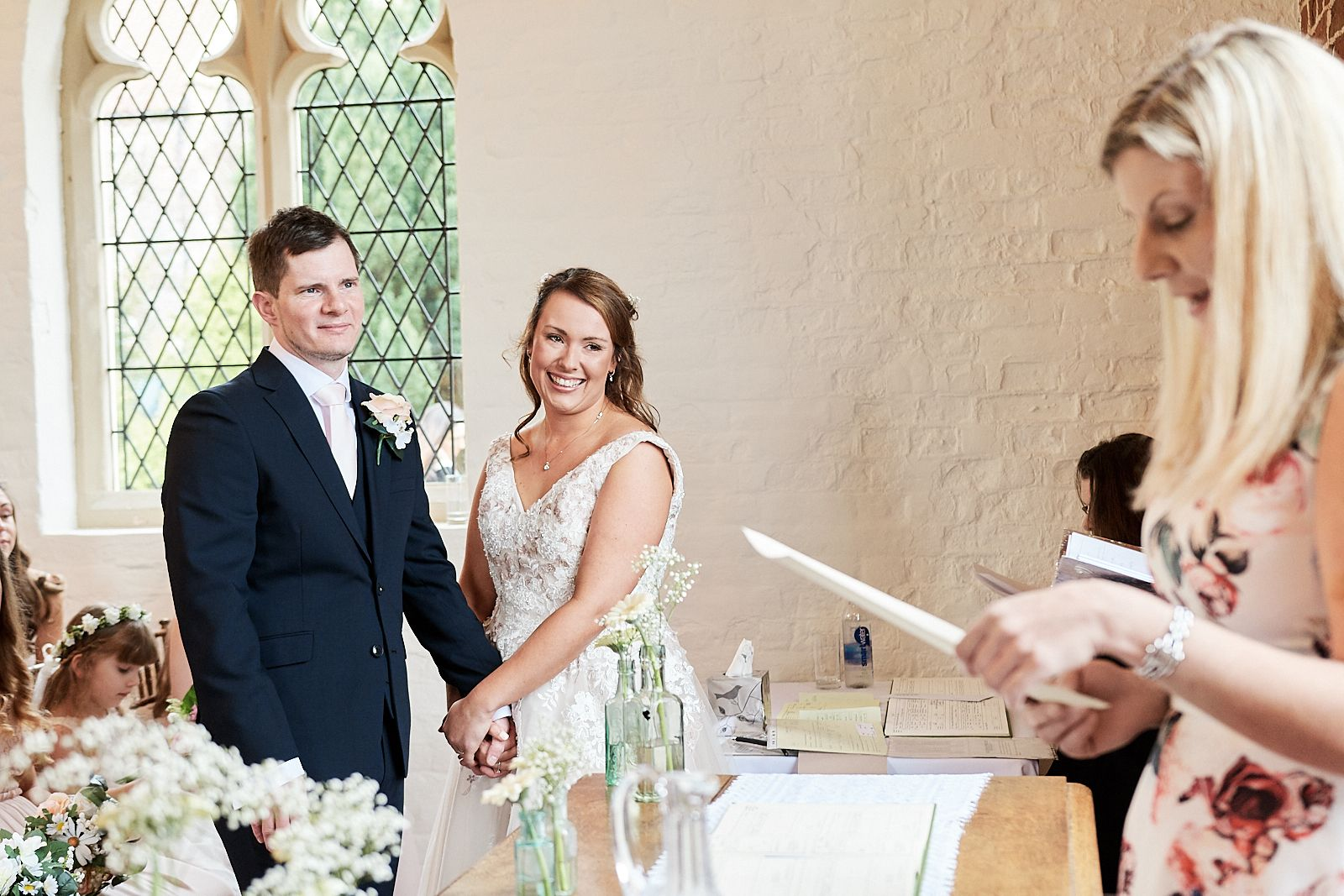 bride and groom hold hands as friend reads at their wedding at The Reading Rooms by Wedding Photographer Faye Amare