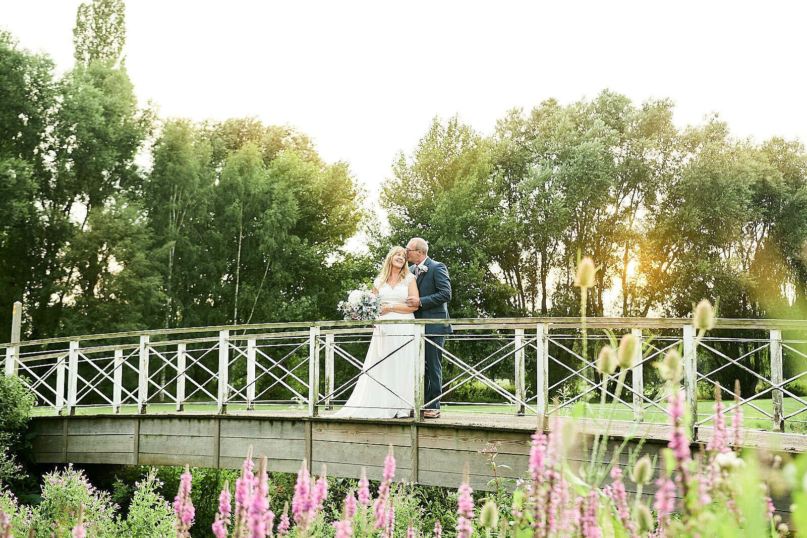 bride and groom share cuddle on bridge at sunset at All Saints Hotel, Suffolk by Norfolk Wedding Photographer Faye Amare